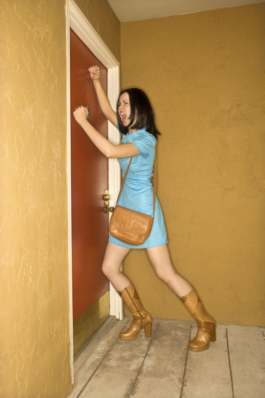 Caucasian young adult woman in retro clothing pounding fists on door and yelling.